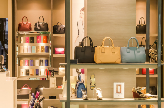 Luxury retail store displaying on shelves women handbags, shoes and purses in different colors