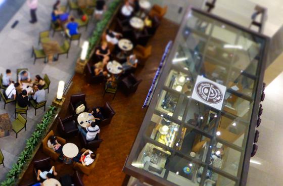 Vue du dessus d'un food court dans un centre commercial avec une multitude de tables et chaises